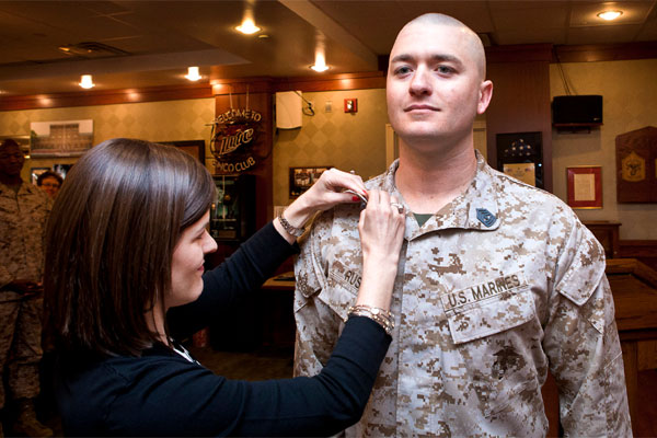 First Sgt. J. Thomas Russo, Company A first sergeant, is pinned to his current rank by his wife, Jennifer, during a promotion ceremony at the Barracks Staff Noncomissioned Officer's Club April 2. (Photo courtesy of Marine Barracks Washington)