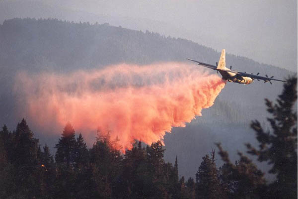 An Air Force C-130 sprays fire retardent over a wildfire area in this file photo. The Air Force is grounding all firefighting-equipped C-130 planes after the fatal crash of one in southwestern South Dakota.
