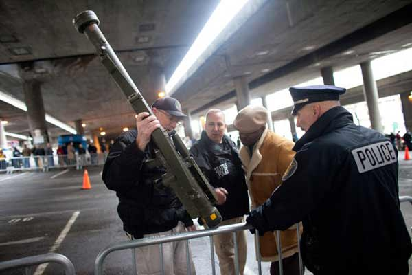 Seattle Police Department officers examine an inert surface to air missile launcher brought to the gun buy back program run by the Seattle Police Department on Saturday, January 26, 2013.