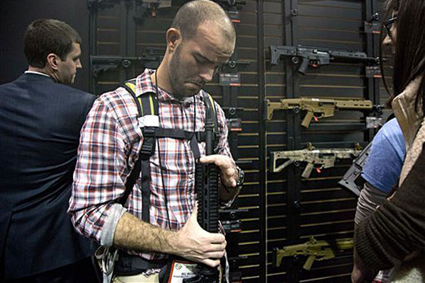 Will Michael of Homer, La., examines a Bushmaster M4 A3 Carbine 300 AAC Blackout rifle at the Bushmaster exhibit during the Shooting Hunting Outdoor Tradeshow, Tuesday, Jan. 15, 2013, in Las Vegas.