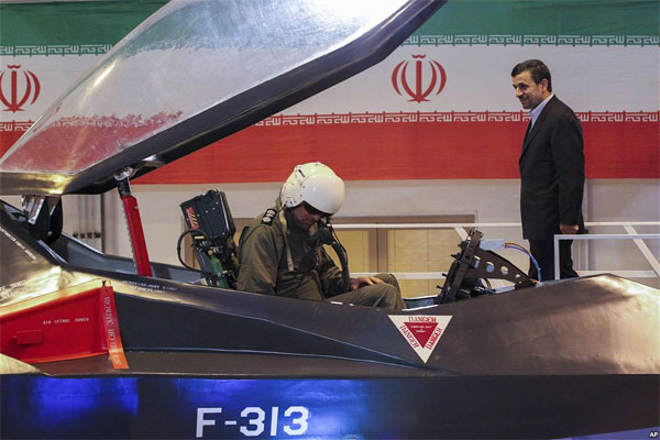 Iranian President Mahmoud Ahmadinejad, center, listens to an unidentified pilot during a ceremony to unveil Iran's newest fighter jet, Qaher-313, or Dominant-313,which officials claim can evade radar, in Tehran, Iran, Saturday, Feb. 2, 2013.