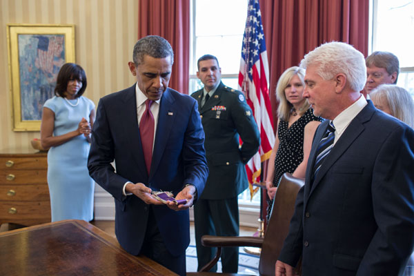 President Barack Obama holds Chaplain (Captain) Emil Kapaun's Easter stole in the Oval Office during a greet with Kapaun's family in the Oval Office, April 11, 2013. (Official White House Photo by Pete Souza)