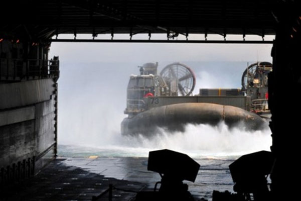 A landing craft, air cushioned, approaches the well deck of amphibious dock landing ship USS Pearl Harbor (LSD 52).