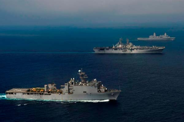 USS Pearl Harbor (LSD 52), front, USS Makin Island (LHD 8) and USS New Orleans (LPD 18) transit in unspecified waters in this official photo of the Makin Island Amphibious Ready Group. (U.S. Navy photo)