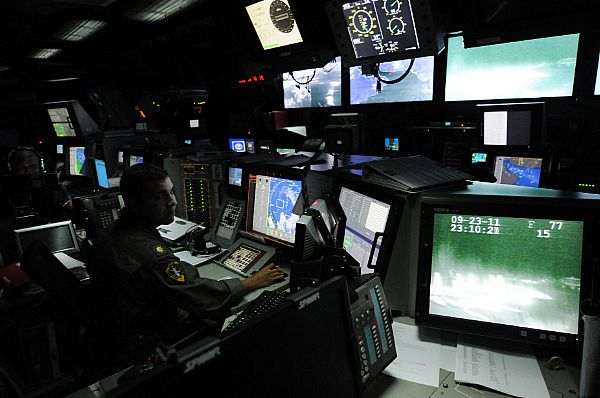 An officer stands watch in a carrier's combat direction center