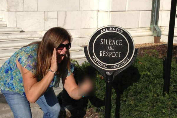 "Lindsey Stone of Plymouth,Mass., pretends to shout while ""flipping the bird"" at Arlington National Cemetery. She and the co-worker who took the photo have lost their jobs at an adult special needs care center since Stone posted the image on Facebook."