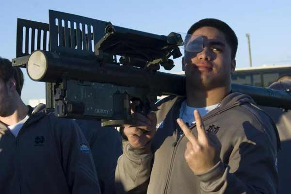 Manti Te'o, a linebacker for the University of Notre Dame Fighting Irish, strikes a pose with some military hardware at the at Abernethy Obstacle Course on Fort Bliss' main post, Dec. 28, 2010