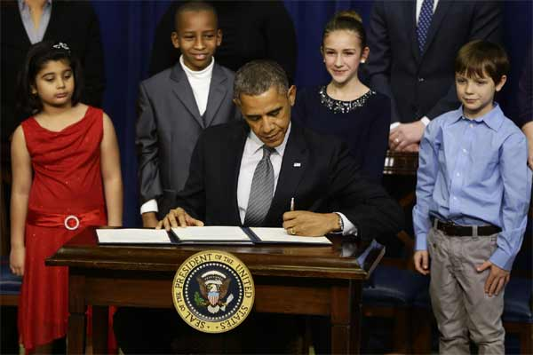 Hinna Zeejah, 8, Taejah Goode, 10, Julia Stokes, 11, and Grant Fritz, 8, who wrote letters to President Barack Obama about the school shooting in Newtown, Conn., watch as Obama signs executive orders outlining proposals to reduce gun violence.