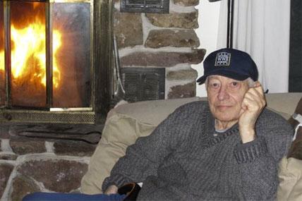 Dr. Rene Joyeuse sits next to a fireplace.