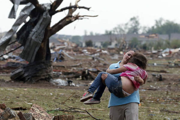 A woman carries a child through a field near the collapsed Plaza Towers Elementary School in Moore, Okla., on May 20, 2013, after a tornado as much as half a mile tore through the community. AP photo
