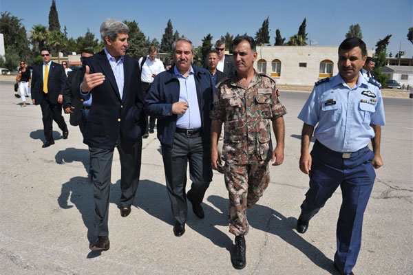 U.S. Secretary of State John Kerry, left, and Jordanian Foreign Minister Nasser Judeh, second left, are escorted by military officers at Marka airport in Amman, Jordan, Thursday, July 18, 2013.