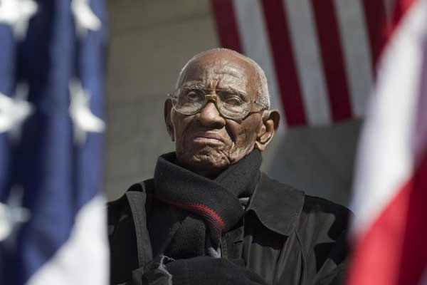 Richard Overton the oldest living WWII veteran, listens during a Veterans Day ceremony attended by President Barack Obama, commemorating Veterans Day, Monday, Nov. 11, 2013, at Arlington National Cemetery.