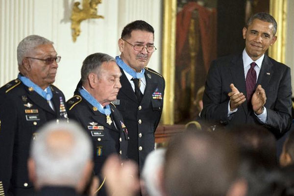 President Obama applauds during a ceremony at the White House, Tuesday, March 18, 2014, honoring Army Staff Sgt. Melvin Morris, from left, Army Sgt. 1st Class Jose Rodela and Army Spc. Santiago Erevia, with the Medal of Honor. (AP Photo/Manuel Balce Cenet