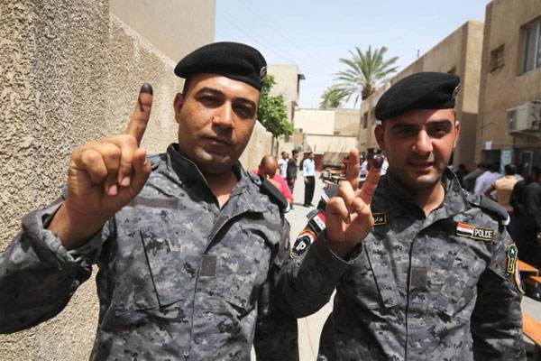 Iraqi police officers show their inked fingers at a polling center in Baghdad, Iraq, Monday, April 28, 2014. Iraqi officials say suicide bombers have targeted polling centers as soldiers and security forces cast ballots ahead of parliamentary elections.