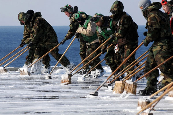 Sailors scrub the flight deck aboard the aircraft carrier USS Ronald Reagan (CVN 76) on March 23, 2011, following a countermeasure wash down to decontaminate the flight deck while the ship was operating off the coast of Japan.