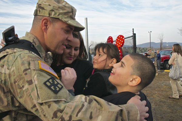Spc. Elias Baez-Cintron, a light wheel mechanic with 333rd Engineer Company, greets his wife and kids during a welcome home ceremony after an 11-month deployment to Afghanistan. Photo by Sgt. 1st Class Julio Nieves
