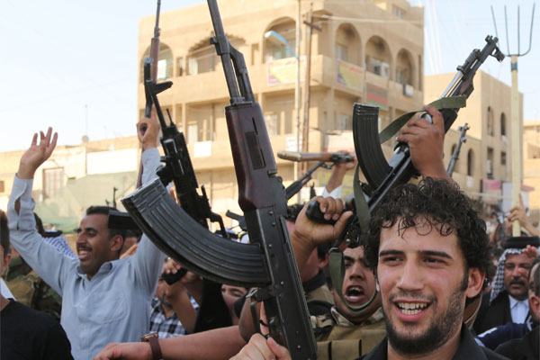Shiite tribal fighters raise their weapons and chant slogans
