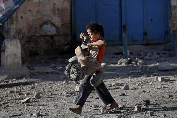 A Palestinian girl walks with a toy that she salvaged from debris of the el-Yazje apartment building which was destroyed following an overnight Israeli missile strike in Gaza City, Thursday, July 17, 2014. (AP photo)