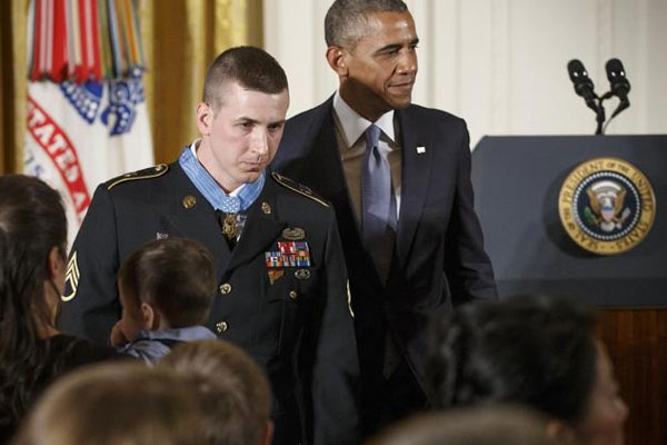President Barack Obama and Medal of Honor recipient, Sgt. Ryan M. Pitts, 28, leave the stage in the East Room of the White House after a ceremony marking Pitts' valor in Afghanistan, Monday, July 21, 2014. AP Photo/J. Scott Applewhite)