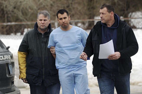 Officials lead Coast Guardsman Adrian Loya of Chesapeake, Va., into District Court Feb. 5, 2015, in Falmouth, Mass., where he was arraigned on charges he killed one woman, injured another and shot a police officer. AP/Cape Cod Times, Merrily Cassidy
