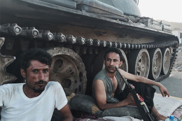 In this March 21, 2015, photo, Members of a militia group loyal to Yemen's President Abed Rabbo Mansour Hadi, known as the Popular Committees, chew qat as they sit next to their tank, guarding a major intersection in Aden, Yemen. (AP Photo/Hamza Hendawi)
