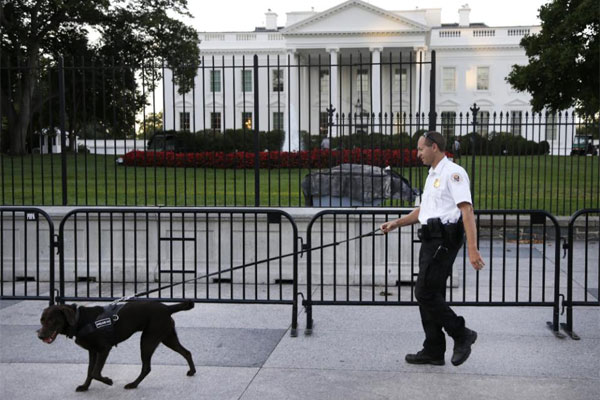 In this Sept. 22, 2014, file photo, a member of the Secret Service Uniformed Division with a K-9 walks along the perimeter fence along Pennsylvania Avenue outside the White House in Washington. (AP Photo/Carolyn Kaster, File)