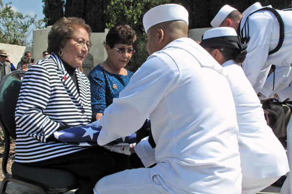 Helen Chavez, the widow of Cesar Chavez receives a flag from the U.S. Navy, honoring her husband's military service during a ceremony in Keene, Calif., Thursday, April 23, 2015. Scott Smith/AP
