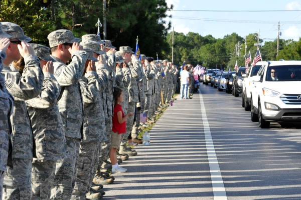 U.S. Airmen from Tyndall Air Force Base, Fla., salute wounded warriors along a parade route as they take part in the Warrior Beach Retreat.U.S. Air Force