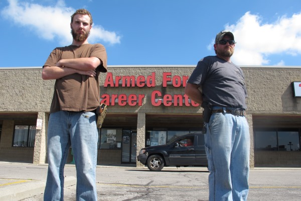Allen Bowles, left, and Clint Janney stand guard outside a military recruiting center in Columbus, Ohio. The men are members of the 3 Percent Irregulars Militia.(AP Photo/Andrew Welsh-Huggins)