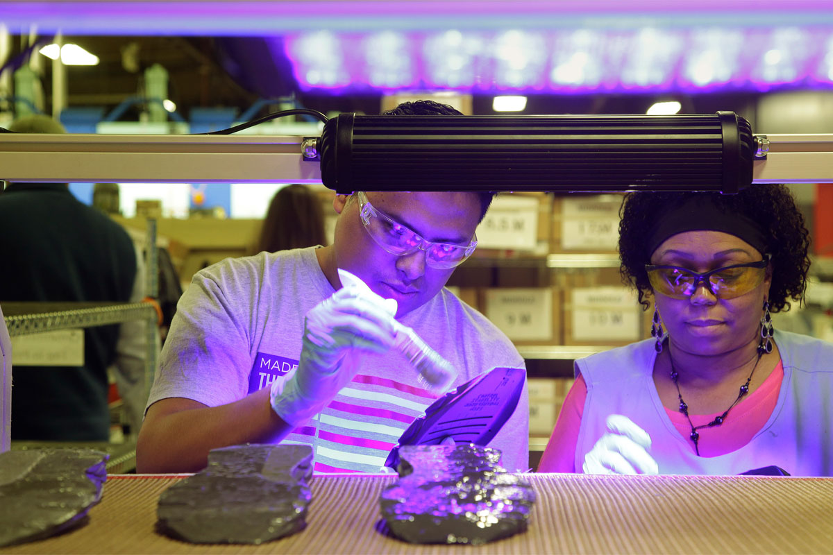 In this photo taken Wednesday July 1, 2015, workers, under ultraviolet light, apply cement to the midsole of the military tested New Balance 950v2 sneaker before the outsole is attached in Boston. (AP Photo/Stephan Savoia)