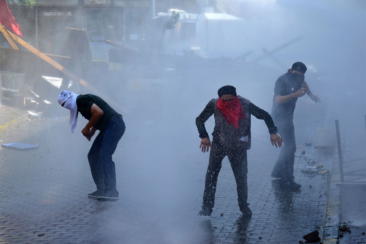 Left-wing protesters try to avoid tear gas and water used by police to disperse them, in Istanbul, Sunday, July 26, 2015, during clashes between police and people protesting against Turkey's operation against Kurdish militants.  (AP Photo/Cagdas Erdogan)