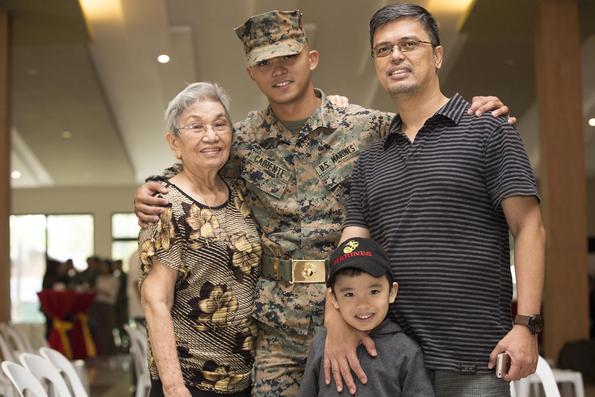 Marine Corps Sgt. Viktor I. Cadiente, a joint fires observer assigned to 3rd Marine Expeditionary Brigade, poses for a photo with his family during the opening ceremony for Amphibious Landing Exercise 2015 at the Philippine Marine Corps Base in Fort Bonif