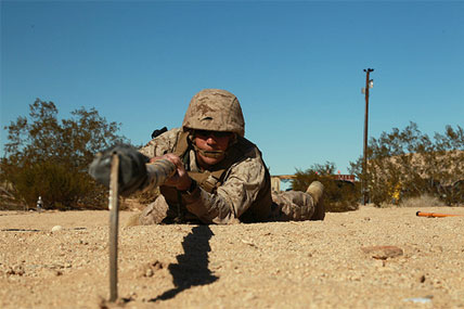 A seaman employs a bamboo sickle to search for buried IEDs at the Combat Center's Range 800.