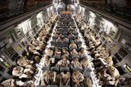 Marines and sit aboard an Air Force C-17 transport aircraft on the flight line at Marine Corps Base Hawaii before departing for Camp Dwyer, Afghanistan, on Oct. 30. (Photo by Cpl. Reece Lodder/Marine Corps)