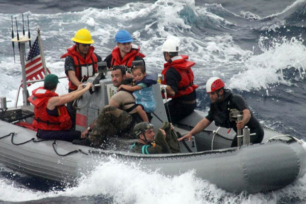 Sailors from Oliver Hazard Perry-class frigate USS Vandegrift (FFG 49) assist in the rescue of a family with a sick infant via the ship's small boat as part of a joint U.S. Navy, Coast Guard and California Air National Guard rescue effort April 6.