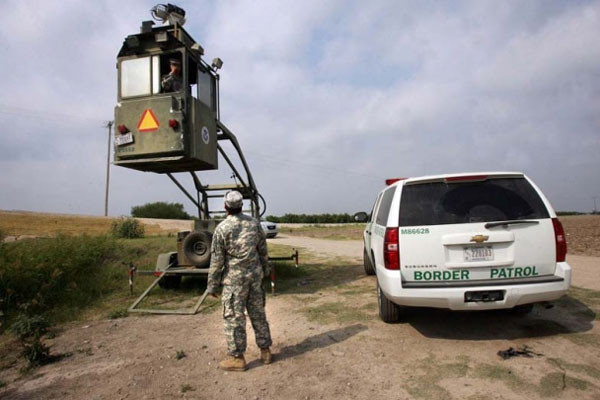 A member of the National Guard checks on his colleague inside a Border Patrol box near the Hidalgo International Bridge in Hidalgo, Texas. (Delcia Lopez/AP)