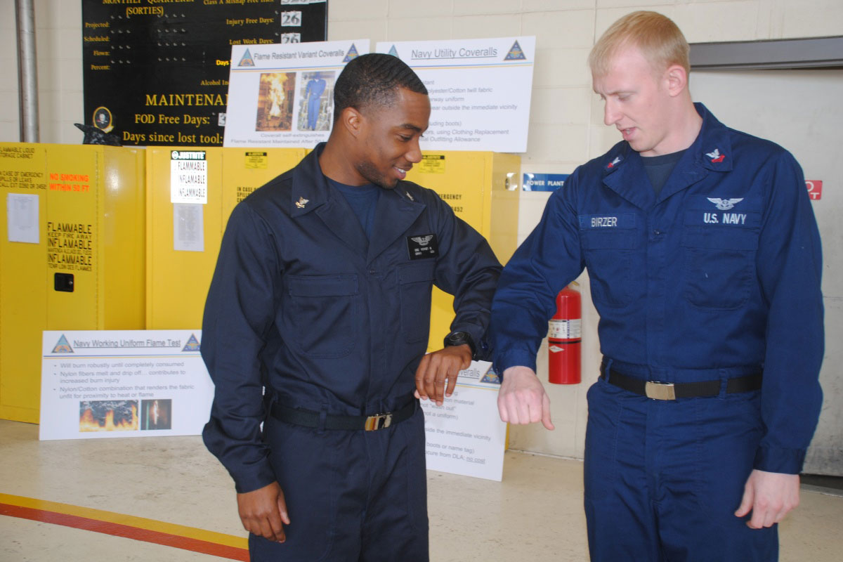 Operations Specialist 2nd Class Martin Vories compares the new flame-resistant variant  coverall with standard coveralls. (U.S. Navy photo by Melinda Larson)