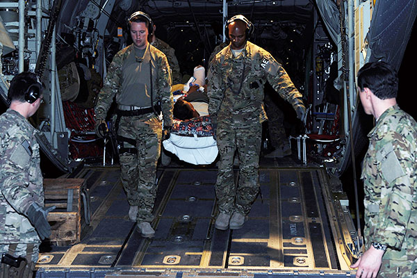 Tech. Sgts. Alexander Finn and Johnny Busby, both 455th Expeditionary Aeromedical Evacuation Squadron aeromedical evacuation technicians, transport a patient from a C-130 Hercules to an ambulance. (U.S. Air Force photo/SSgt. Whitney Amstutz)