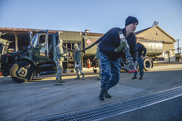 Petty Officer 3rd Class Christian Fakhoury, a Naval Air Field Atsugi Carrier Airborne Early Warning Squadron administrative assistant, pulls a fuel hose for daily inspection at Yokota Air Base, Japan. (U.S. Air Force/Senior Airman David Owsianka)