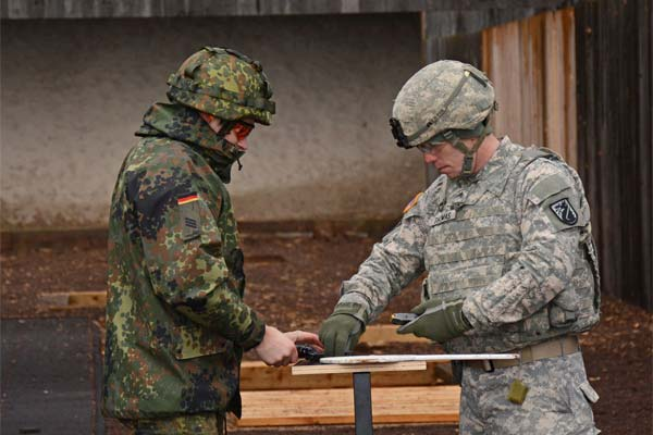 Sgt. Bryan G. Thomas helps Cpl. Manuel Marx, clerk, Public Affairs Office, Hessen State Command safely through each step of qualification process during a M9 combat pistol qualification range (Staff Sgt. Marshall R. Mason)