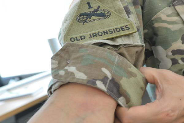 A Soldier demonstrates how the sleeves can be rolled with camo out, no more than three inches above the elbow. (Photo Credit: Gary Sheftick)