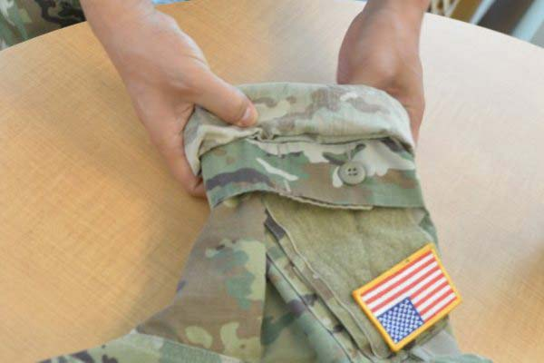 A soldier demonstrates how to roll up the ACU sleeves so that the top portion can be pulled down over the roll for camo out. (Photo by Gary Sheftick/U.S. Army)