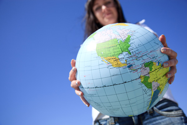 Girl holding a beach ball globe.