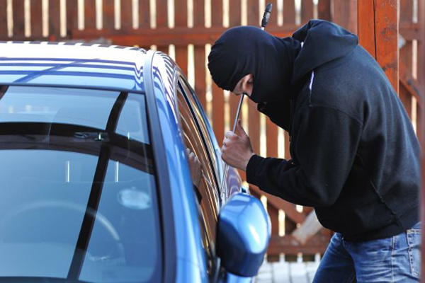 Car thief wearing a black hoodie.