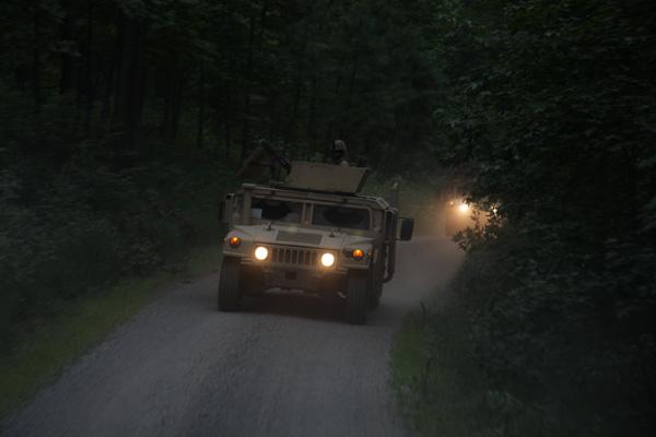 Humvee with headlights on at night.