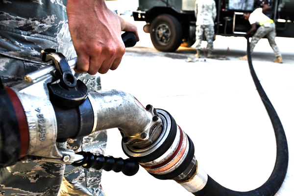 Servicemembers connect a fuel line.