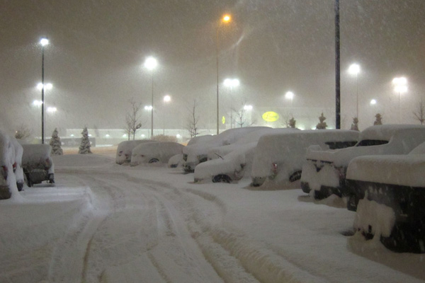Snow covering cars in piles.