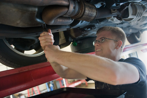 Car mechanic repairing the underside of the car.