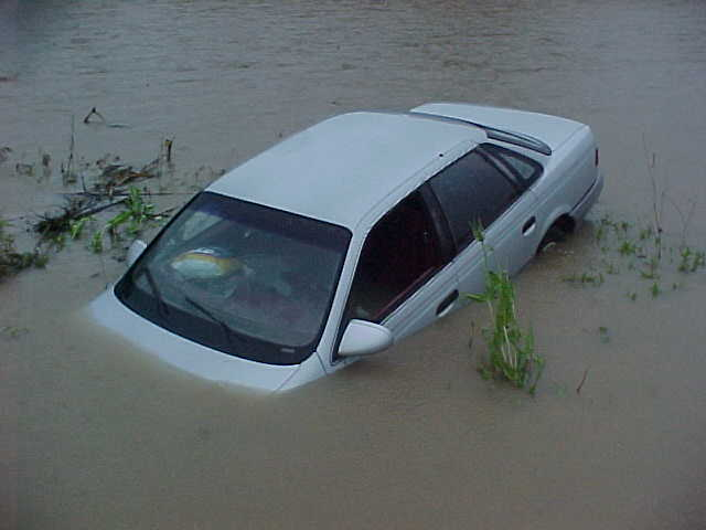 Silver car submerged in water.