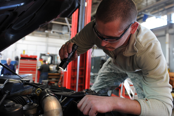 Service member repairing auto engine with a flashlight.